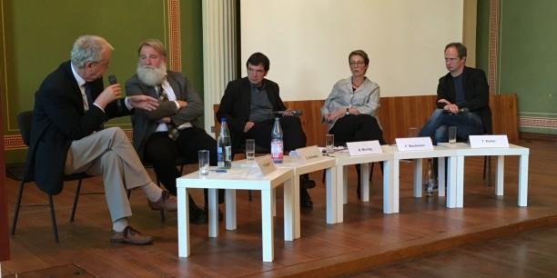 """Engagierte Diskussion zu """"Kirche im Kapitalismus?"""" auf dem Podium im Löwengebäude der Martin-Luther-Universität Halle-Wittenberg."""