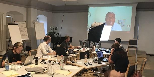 Sonst vollbesetzt, in diesem Jahr aber zum Studio umfunktioniert: Das Organisationsteam der Sommerakademie während der Live-Übertragung einer Online-Podiumsdiskussion im Chorsaal des Zinzendorfhauses. Foto: (c) Eleonore Roderfeld/EAT.
