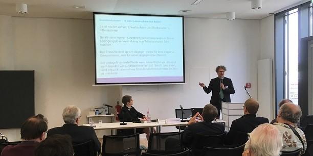 Michael David stellt beim Fachtag Grundeinkommen in Berlin die Fragen vor, die bis zur Verabschiedung einer neuen Grundsatzposition der Diakonie zum Grundeinkommen bearbeitet werden. Foto: © EAT.