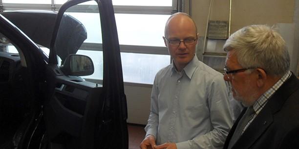 Geschäftsführer Stephan Warmuth erläutert Propst Diethart Kamm die Umbaumaßnahmen an behindertengerechten Fahrzeugen.