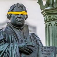 Martin Luther in Wittenberg. Die Figur Luthers trägt eine gelbe Augenbinde. Diese Aktion war ein Aufruf, um sich von Luthers Judenhass zu distanzieren. Die gelbe Binde zeigt Luthers Blindheit den Juden gegenüber. Foto: © Alexander Baumbach